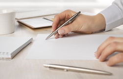 女商人在纸的手文字特写镜头在书桌 免版税库存图片