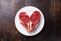 心脏形状在板材的生肉牛排 免版税库存照片