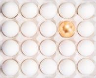 金子在许多白鸡蛋之间的复活节彩蛋 库存图片