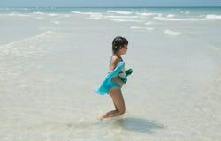 走在海洋的儿童女孩在夏天晴朗的华美的天 免版税库存照片