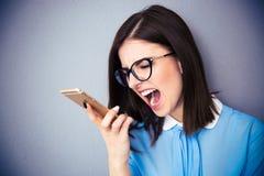 呼喊在智能手机的恼怒的女实业家 免版税库存图片