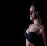 一个美丽的性感的女孩的剪影黑女用贴身内衣裤有卷毛的和明亮的构成的与在您的面孔的微笑在黑背景 图库摄影