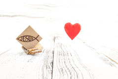 Христианский символ рыб высек в древесине на белой винтажной деревянной предпосылке Стоковое фото RF