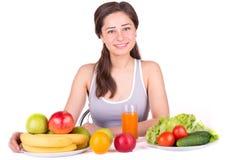 Όμορφο κορίτσι με τα φρούτα και λαχανικά στον πίνακα Στοκ Φωτογραφίες
