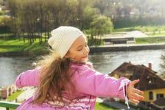 逗人喜爱的小女孩发光了充满幸福,卷发,迷人的微笑在晴朗的春日 免版税库存图片