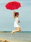 跳跃与在海滩的伞的红发女孩 免版税库存图片