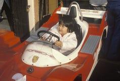 驾驶一辆碰撞用汽车的一个亚裔美国人孩子在圣塔蒙尼卡码头,加州 库存照片