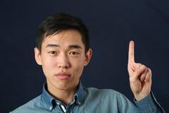 向上指向他的食指的滑稽的年轻亚裔人 免版税库存照片