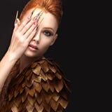 Красивая девушка в изображении Феникса с ярким составом, длинными ногтями и красными волосами Сторона красотки Стоковые Изображения RF