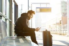Χαμογελώντας νεαρός άνδρας με το κινητές τηλέφωνο και την τσάντα Στοκ εικόνες με δικαίωμα ελεύθερης χρήσης