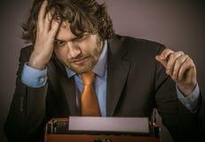 Ματαιωμένος επιχειρηματίας που κοιτάζει επίμονα στη γραφομηχανή του Στοκ εικόνα με δικαίωμα ελεύθερης χρήσης