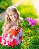 Χαμογελώντας όμορφο μικρό κορίτσι που κάθεται οκλαδόν και που κρατά το πορφυρό λουλούδι Στοκ Εικόνες