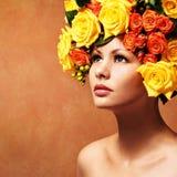 有黄色玫瑰的妇女 有花头发的式样女孩 免版税库存照片