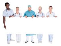 举行招贴的小组多种族医生 免版税库存照片