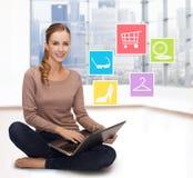 有膝上型计算机的在家在网上购物微笑的妇女 库存照片