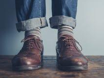 一个人的脚在木地板上的 免版税库存照片