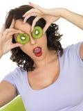 拿着在眼睛的健康少妇新成熟猕猴桃切片 图库摄影