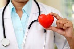 举行美好的红色心脏形状的女性医生 免版税库存图片