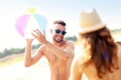 Молодые пары играя с шариком на пляже Стоковые Изображения RF