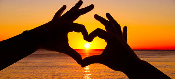 现出轮廓在心脏形状的在海洋的手和日出 免版税库存图片