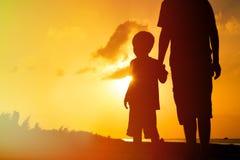 握手的父亲和儿子在日落海 免版税库存图片