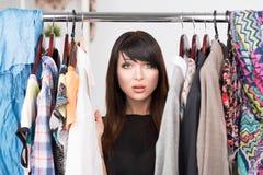 年轻迷茫的妇女画象在衣橱前面的 免版税库存照片