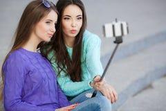 拍与您的智能手机的两个少妇照片 库存图片