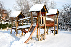 儿童操场在用冬天雪盖的公园 免版税图库摄影