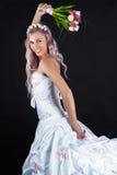 跑与郁金香花束的愉快的新娘  免版税库存照片