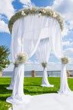 在绿色草坪的婚礼设置 白色婚礼曲拱 库存照片