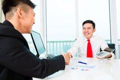 亚裔银行家劝告在金融投资 库存照片