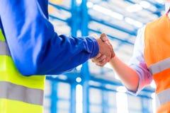 工作者和工程师握手在工厂 库存照片