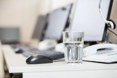 在书桌上的水玻璃在电话中心 库存图片