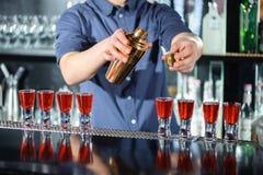 男服务员做在酒吧的射击 免版税库存图片
