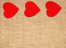 毗邻红色心脏框架在大袋帆布粗麻布背景的 免版税库存照片