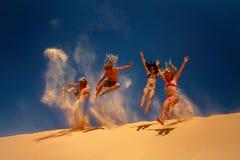 跳在黄沙沙丘的朋友 免版税库存图片