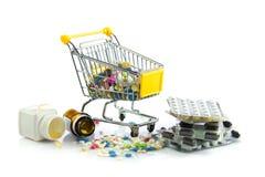 有在白色背景隔绝的药片的购物台车使医学服麻醉剂 免版税图库摄影