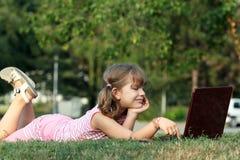 说谎在与膝上型计算机的草的小女孩 免版税库存图片