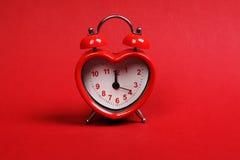 爱的时刻 在红色背景的红色心形的闹钟 免版税图库摄影