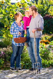 家庭从事园艺,站立与叉子在庭院里 免版税库存照片