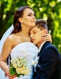 新娘和新郎与室外的花 免版税库存照片