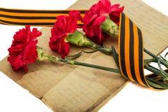 康乃馨、老信件和圣乔治丝带 免版税库存照片