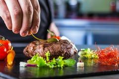 Αρχιμάγειρας στο μαγείρεμα κουζινών ξενοδοχείων ή εστιατορίων, μόνο χέρια Έτοιμη μπριζόλα βόειου κρέατος με τη φυτική διακόσμηση Στοκ Εικόνα