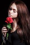 一个苍白美丽的少妇的特写镜头画象有一朵红色玫瑰的 免版税库存图片