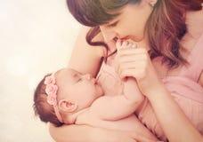 有同情心的她逗人喜爱的睡觉的女婴的母亲亲吻的手指 免版税库存图片