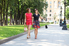 走在夏天城市的两个愉快的少妇 免版税库存图片