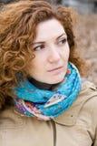 一个年轻美丽的红发女孩的画象一条明亮的围巾的 免版税库存图片