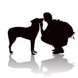 Силуэт молодого человека с собакой Стоковая Фотография