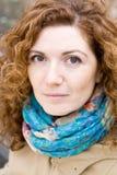 一个年轻美丽的红发女孩的画象一条明亮的围巾的 库存照片