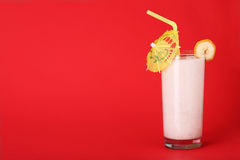 圆滑的人在红色的香蕉味道健康玻璃  免版税图库摄影